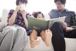 父親、母親、娘がソファーに座っている図
