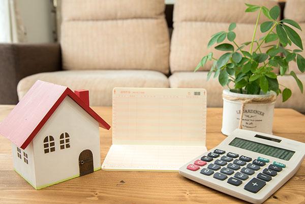 家の模型と通帳、電卓の図